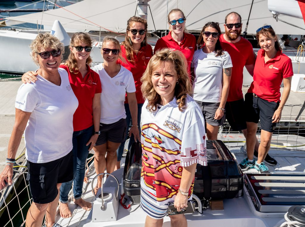 Yvonne Weldon stands centre frame. Behind her, all also standing on the boat, are the Maiden crew. Wendy Tuck is on the far left.