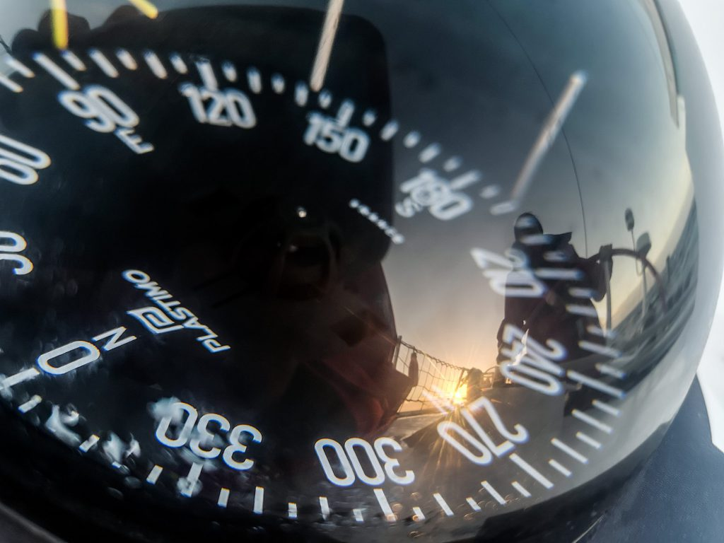 A compass, reflecting Maiden's skipper Wendy Tuck, who is at Maiden's helm. There is a sunset in the background
