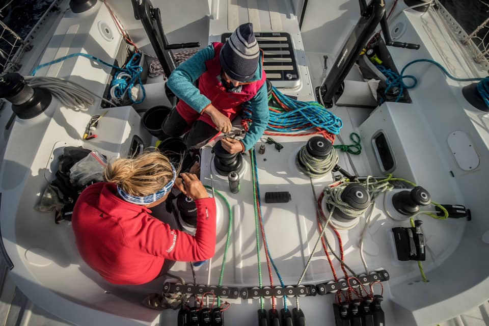 Two sailors sit on the deck of the yacht Maiden. They are both working on winches. The deck has a lot of ropes everywhere, and it is clear there is a lot of work going on.