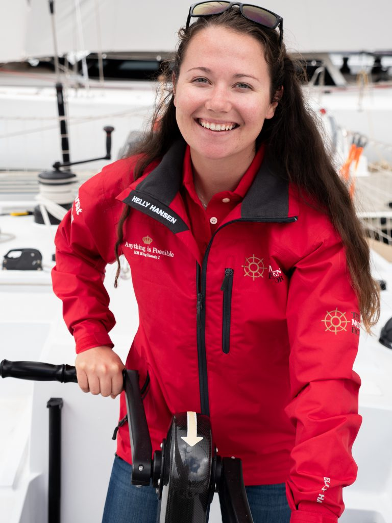 Alison stands at the grinder, with both hands on either side. She had sunglasses on her head and is smiling. She wears a red Maiden jacket with a red polo underneath. Her hair is down.