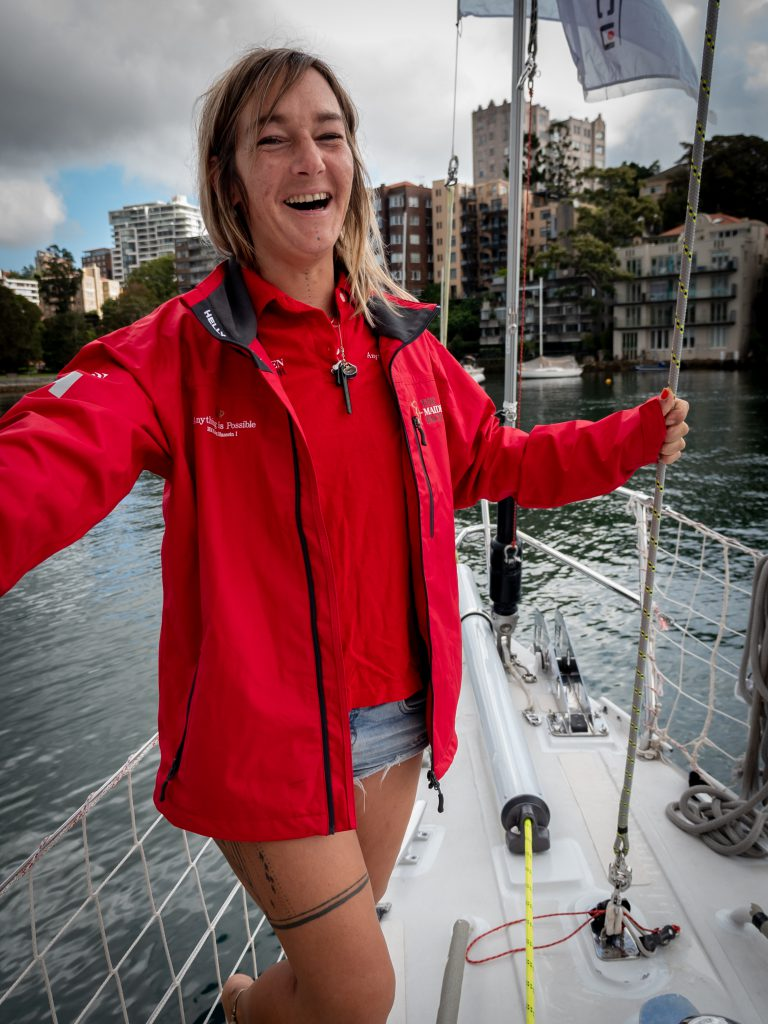 Alex stands at the front on Maiden, holding one of the lines. She is wearing a red Maiden jacket and polo. Her necklace hangs on her polo. She is laughing and looking happy.