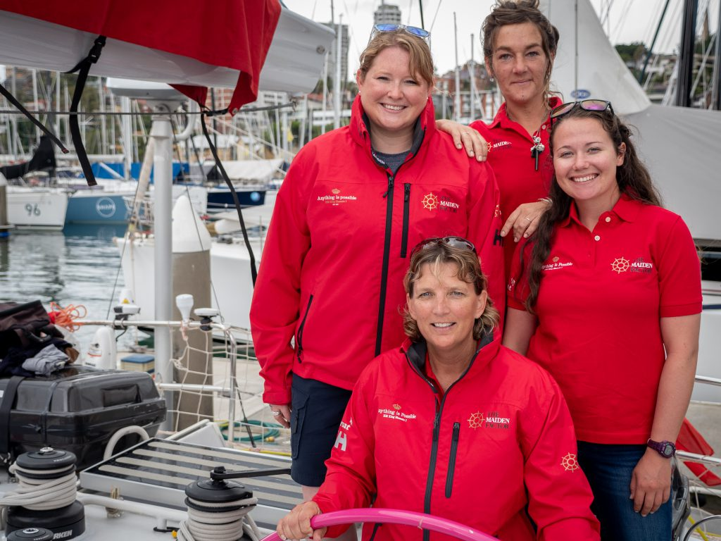 Sharon Ferris Choat stands at Maiden's helm. Behind her and to the left is Kate, then Alex, then Alison. They are all wearing red t-shirts and coats.