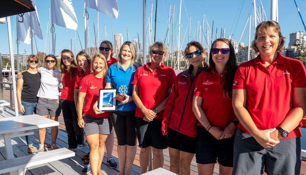 All the Maiden crew stand in a line. In the middle is Rear Commander Janey Trevelean, holding a trophy and a photo of Maiden. Everyone is smiling.