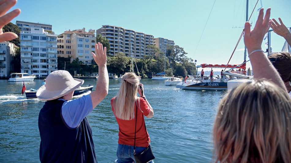 People on dock wave goodbye to the Maiden yacht. People's hands are in the air, with a girl taking photos in the middle. In the background are buildings