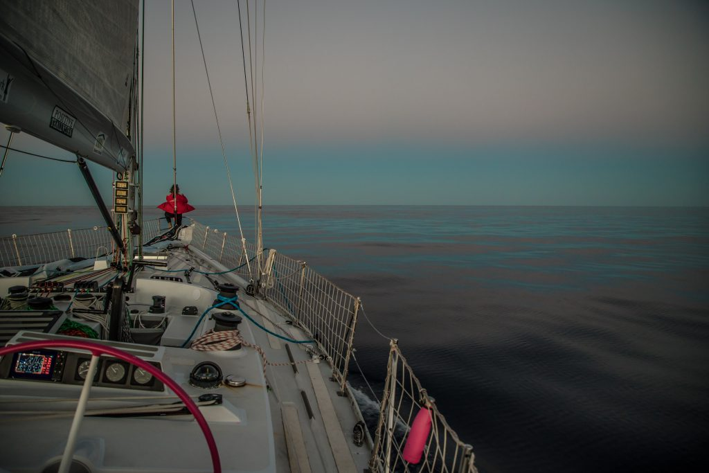 Maiden is on the left of the image. The photo is taken from the helm. At the front of the boat, a sailor stands. The water is reflecting the sea.