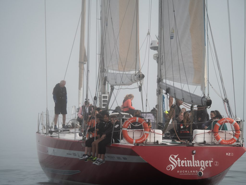 Steinlager on a foggy sea. Students sit on the side of the boat with their legs over the edge