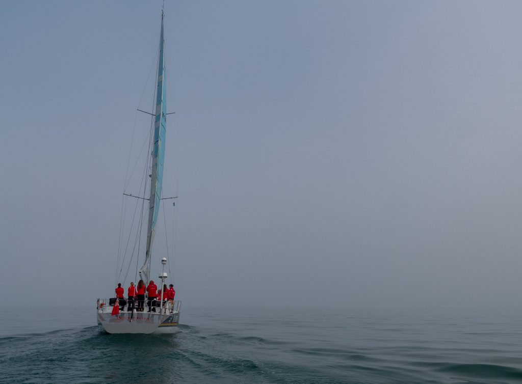 Maiden sails into the blue. A calm day and a foggy sky