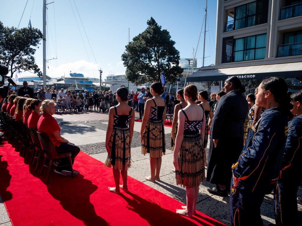 Students stand waiting in traditional Powhiri dress. The Maiden crew sit on chairs to the left, on a red carpet