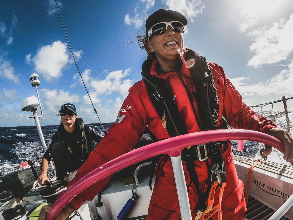 Sharon Ferris-Choat is at Maiden's helm. She's wearing sunglasses, a lifejackets and her red jacket. The sky is blue but dramatic. Belle sits behind in blue, wearing a lifejacket, hat and sunglasses.