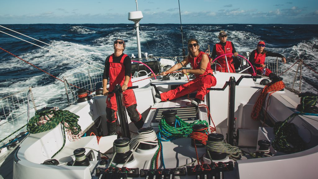 Four sailors on Maiden at the back. One on the grinder, one holding a rope, one at the helm and one sitting at the back.