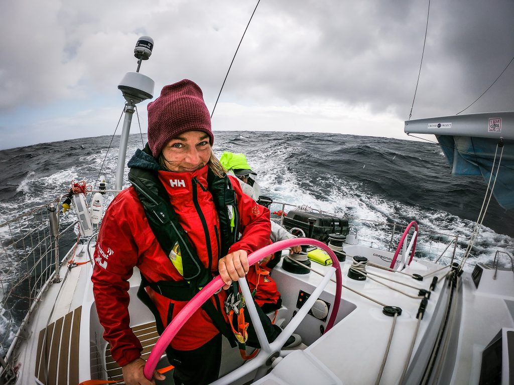 Alex Greu, wearing a red hat and maiden jacket, with a lifejacket, is at Maiden's Helm