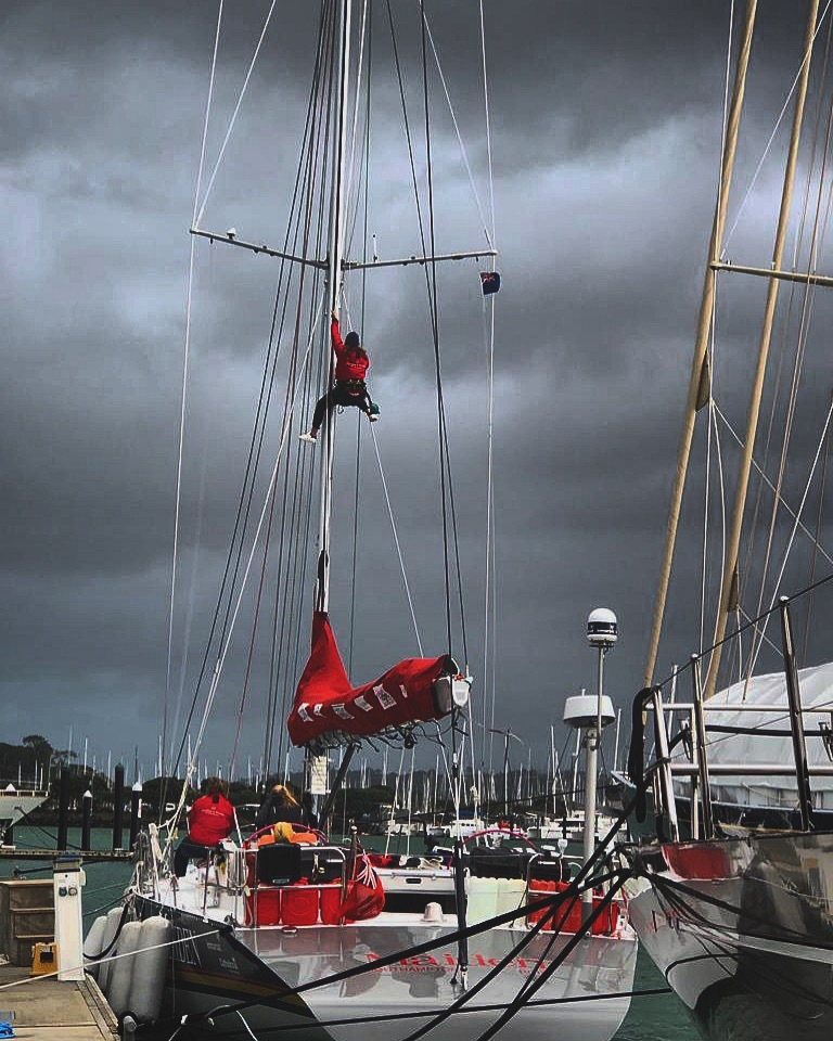 Stormy weather behind Maiden in a harbour. A crew member is halfway up the mast