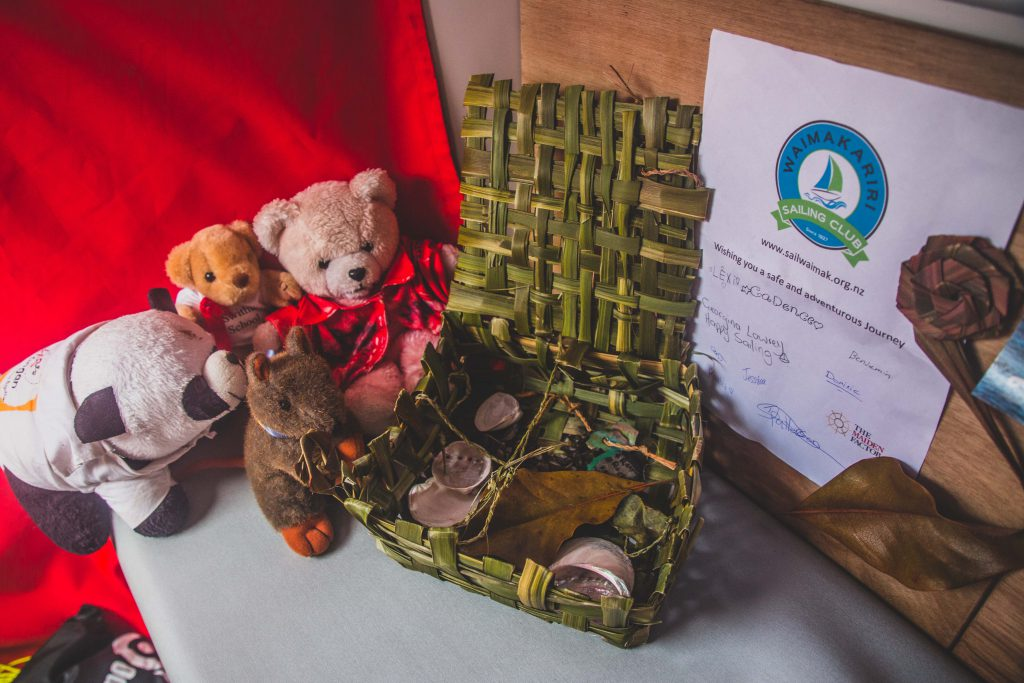 A green flax box holds shells and leaves, with mascots next to it. Mascots are two teddies, a kangaroo and a panda