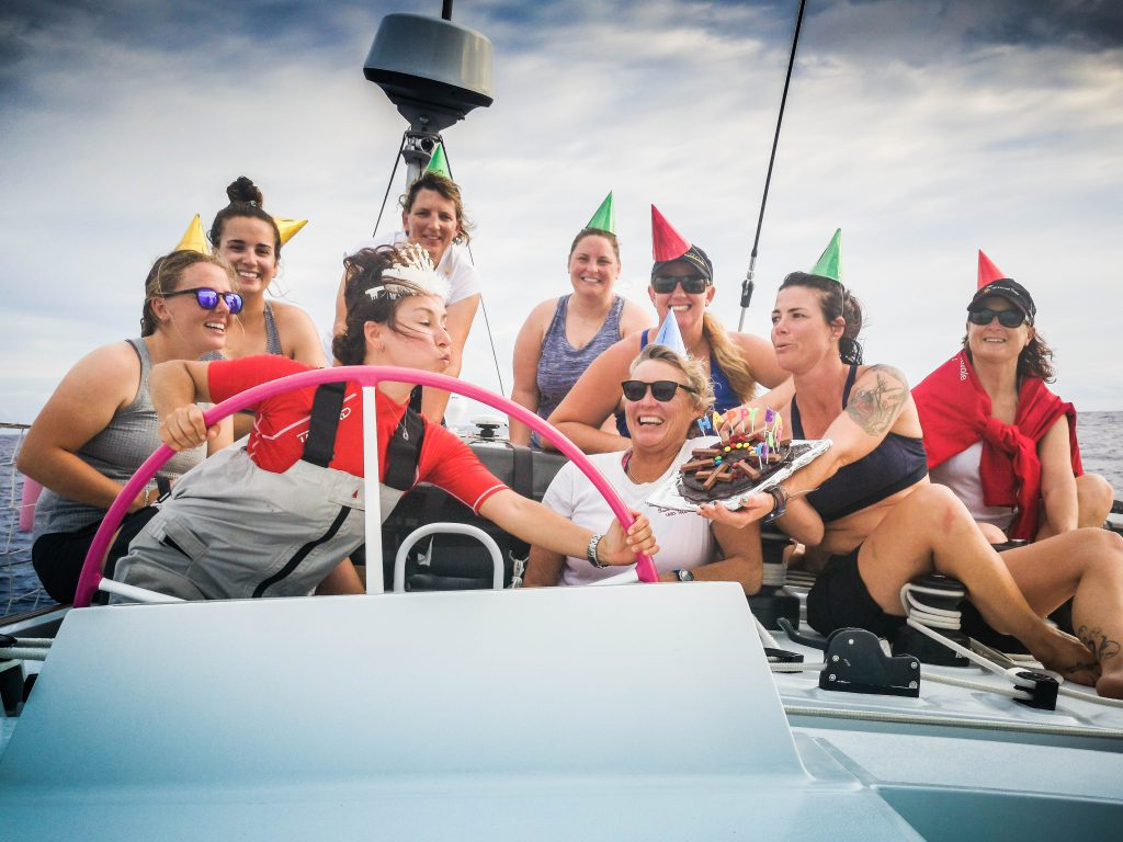 The Maiden crew all wear party hats for Amalia's birthday. She is at the helm, blowing out candles on a cake that Belle is holding.