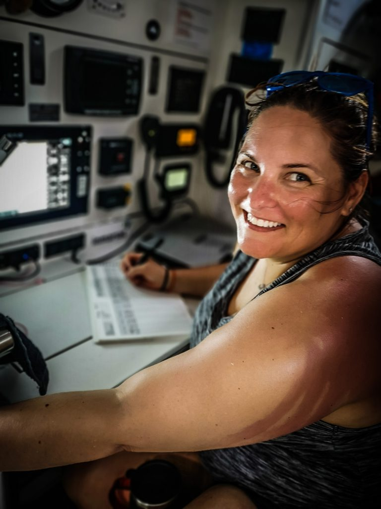 Down below deck, a sailor is writing and smiling at the camera. The nav station is behind, with lots of equipment.