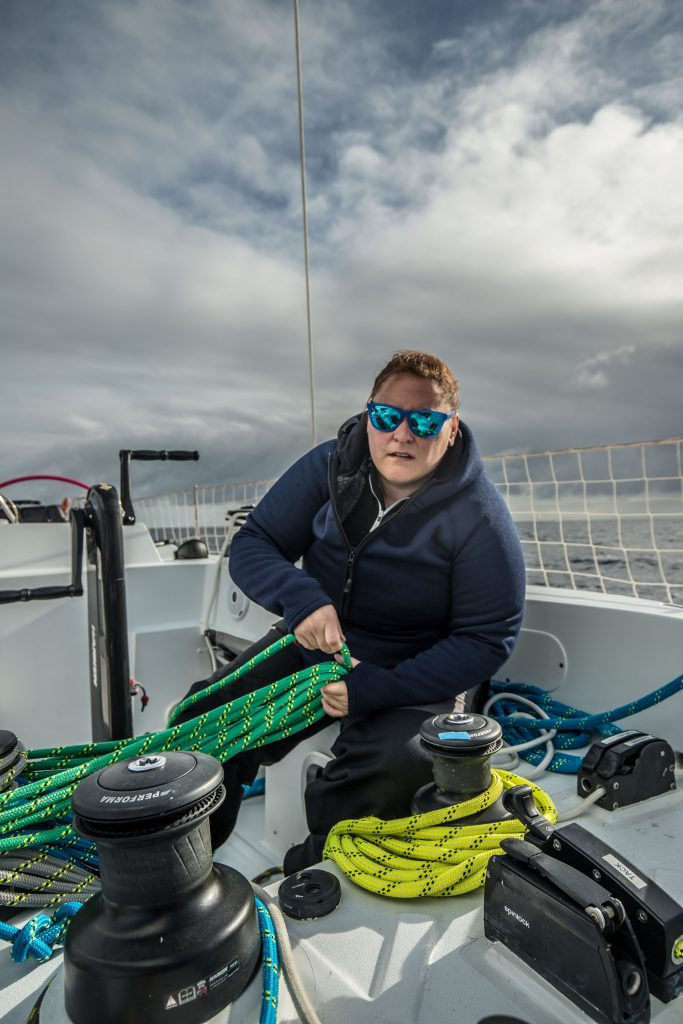 A sailors on Maiden is working with ropes on deck. She wears reflective blue sunglasses and warm clothing.