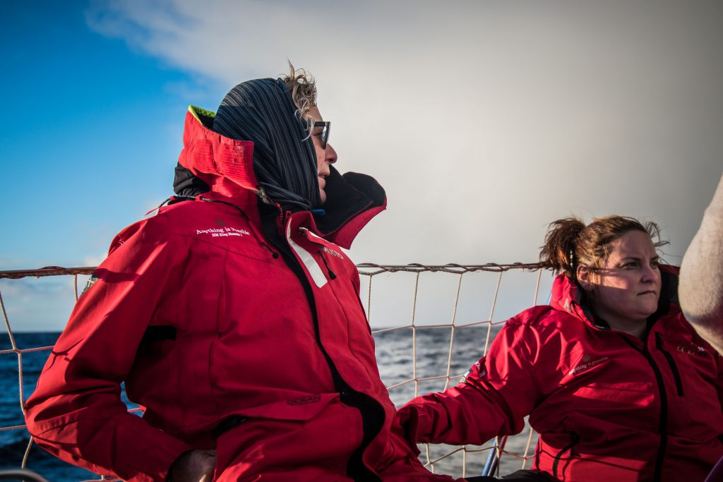 Two sailors lean against the string fence around Maiden's edge. Behind is the cloudy sky and dark sea.