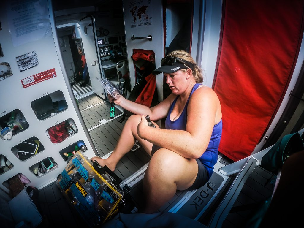 A sailor sits on the floor, working with a toolbox in front.