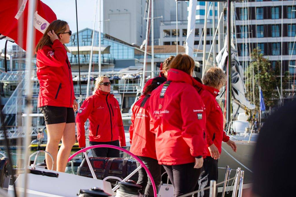 A group of sailors in red jackets stand onboard Maiden. Maiden's pink wheel is clear in the middle. The view behind is busy, with a lot of buildings and yachts.