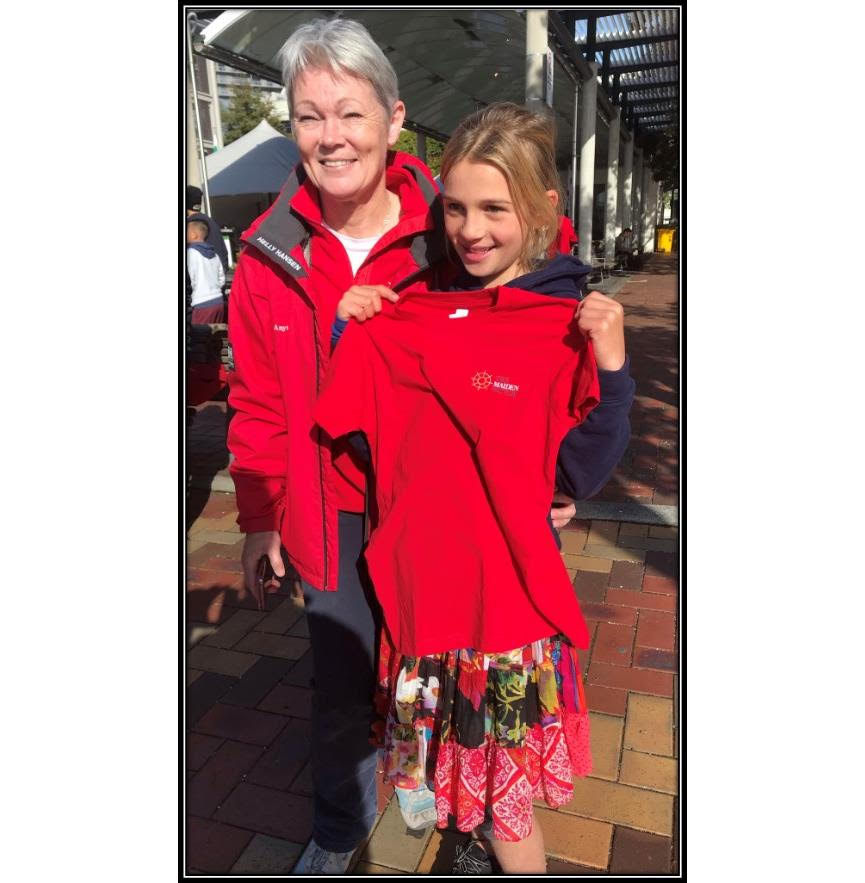 Tracy Edwards stands next to a young girl. Tracy is wearing a red jacket and fleece. The girl is holding up a red t-shirt