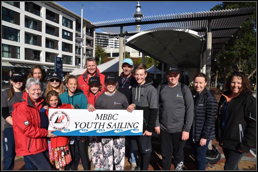 A group from MBBC stand on the Viaduct harbour, holding a MBBC sign