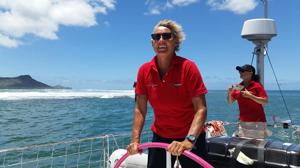 Wendy Tuck at Maiden's helm, hair windswept and smile large. There's a hill in the distance and a blue blue sea.