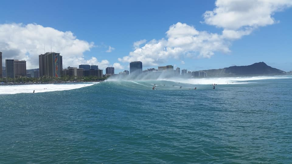 Wow! Surfers skate over large waves as the spray shines in the air. Behind, the grey city juxtaposes the bright blue ocean.
