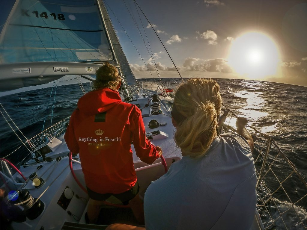 Two sailors, Wendy at the helm. Wearing a red jacked. The sun is very large and is setting on the left of the image.