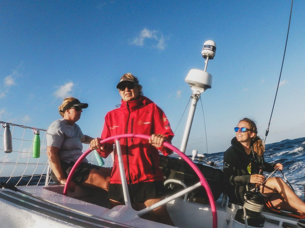 Wendy, skipper in red jacket, stands at maiden's helm holding the wheel. Two sailors smile next to her.