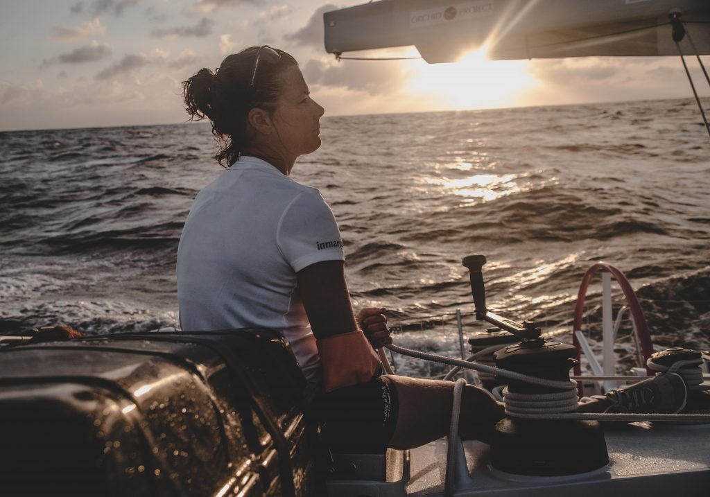 Belle sits holding a rope attached to the winch. Her arm is in a sling. The sun is setting.