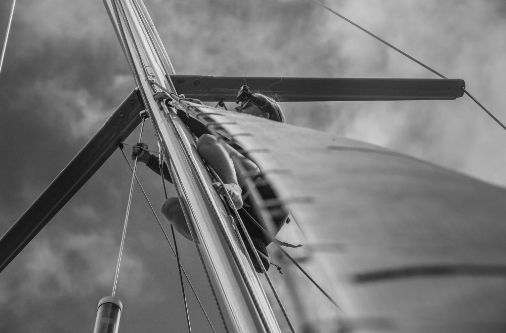 Up the helm, black and white, the sail obscures most of the sailor.