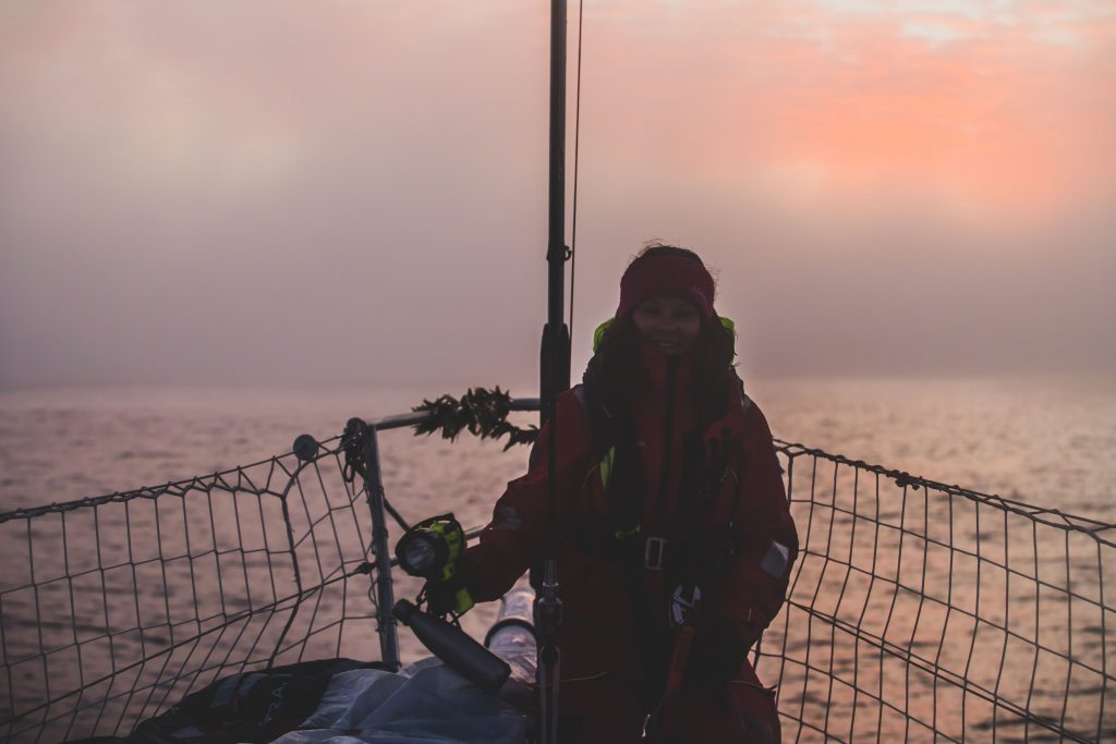 Theresa sits at the bow of the boat, with a sunrise behind. It is a ocean sea and she smiles, wrapped up warm with a torch in hand.