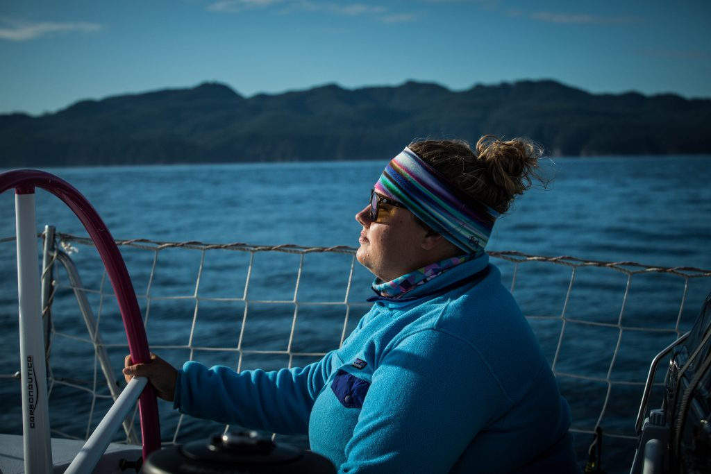Kirsten at the helm, taken side on. She wears blue, wears glasses and a headband and holds the wheel. Islands are in the background