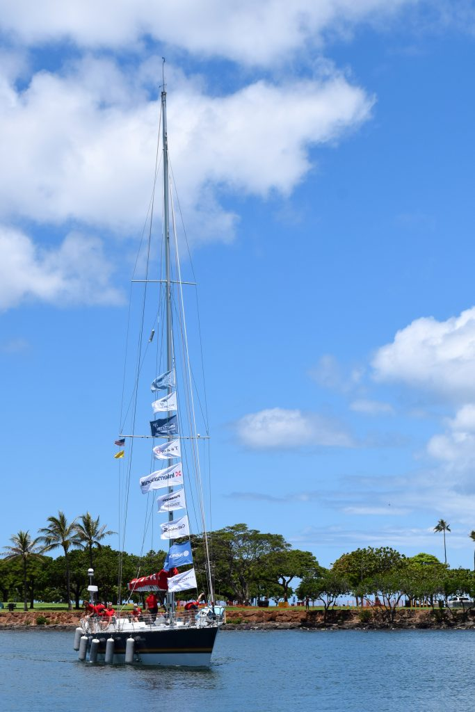 Maiden sails in on a blue calm water with a bright blue sky. Palm trees are behind