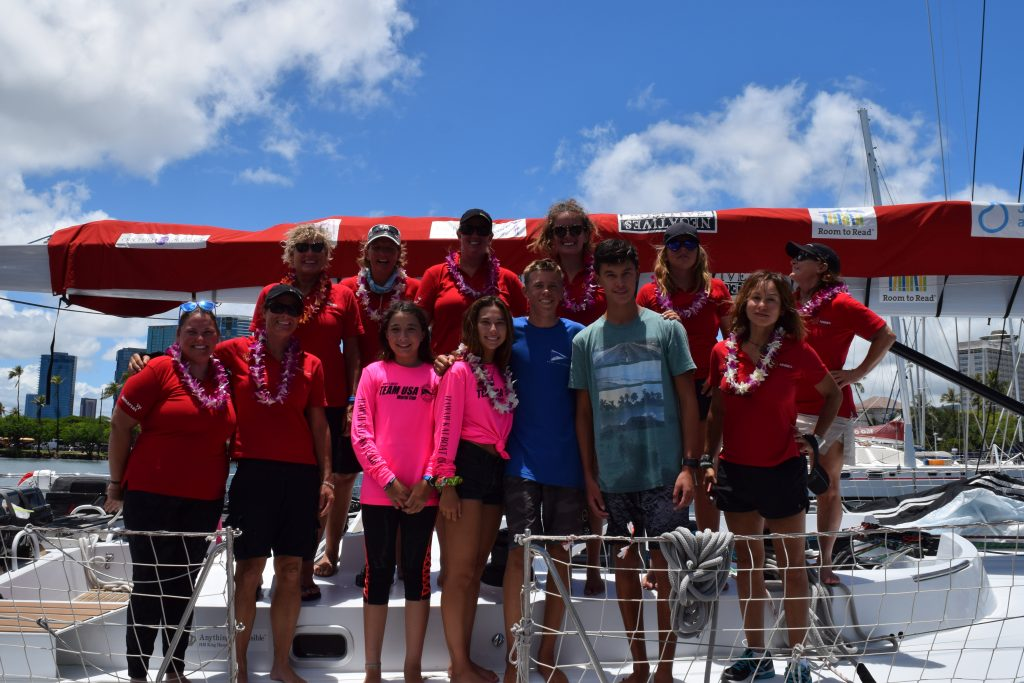 All smiles and leis, with youngsters from the Hawaii yacht club. The Maiden crew stand on deck with a bright blue sky backdrop.