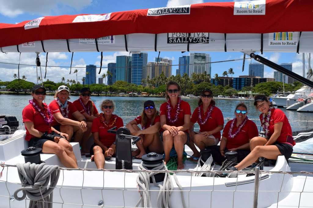 All smiles as Maiden sailors sit on deck, under the charity logos on the boom.