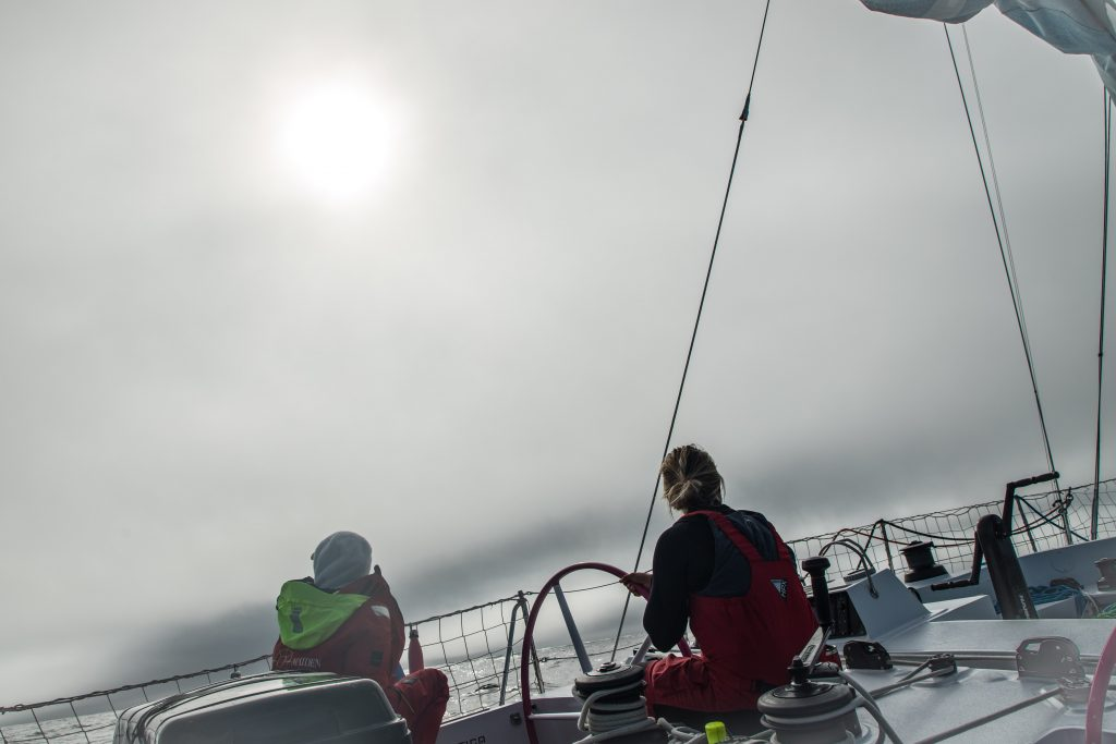 A grey foggy morning with the sun behind the clouds. Two crew members are on deck