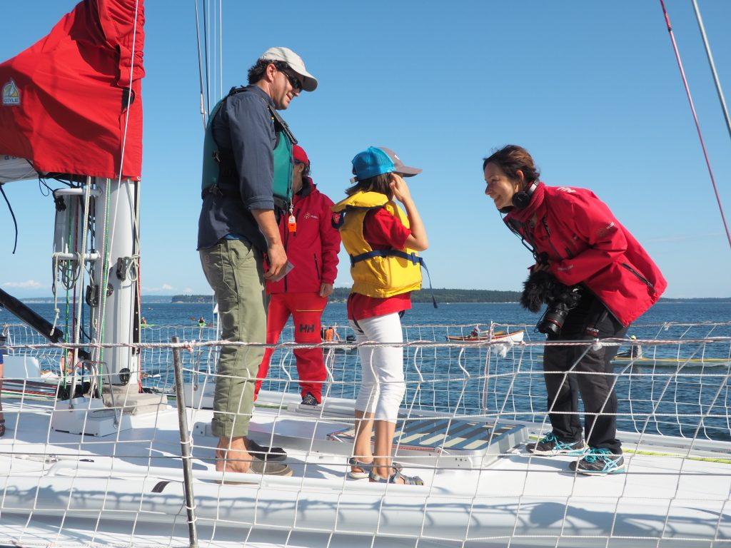 Amalia bends down to speak to a young sailor onboard Maiden