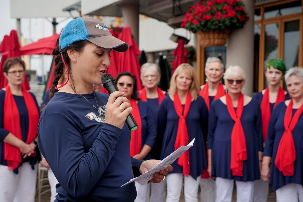 Jeanne stands in front of the choir who are in red blue and white. Jeanne reads from a piece of paper, smiling, holding a microphone.