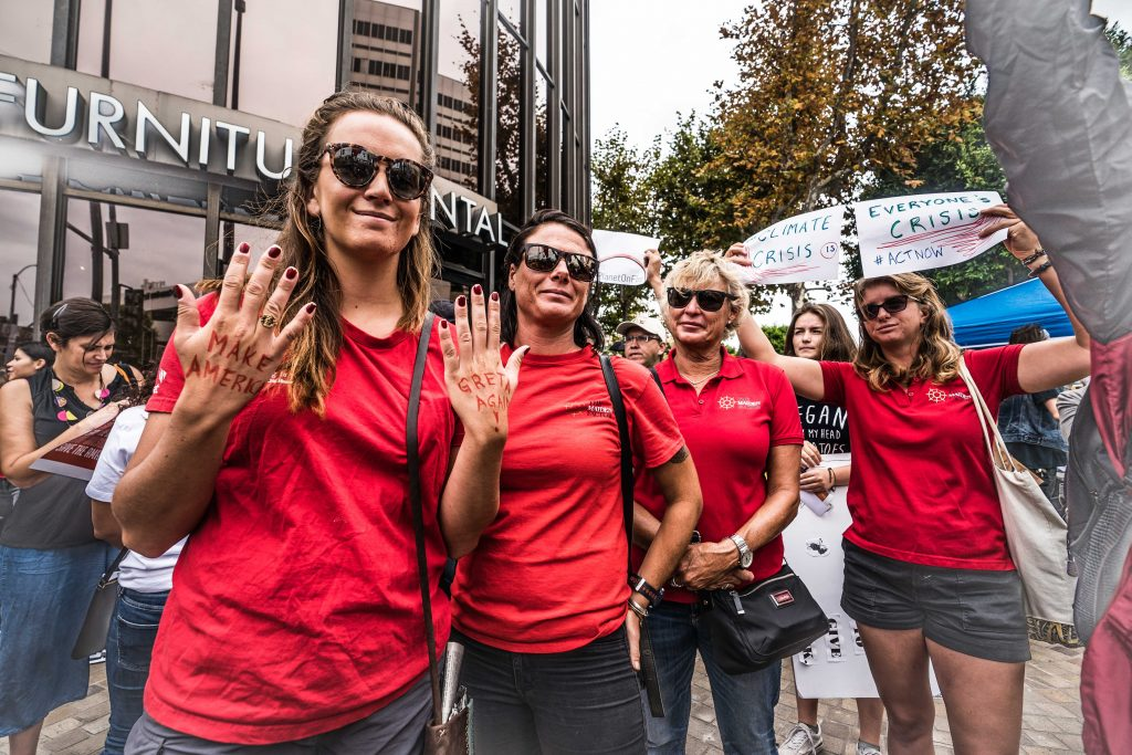 Maidens in red t-shirts smiling. Courtney has 'make America greta again' written on her hands