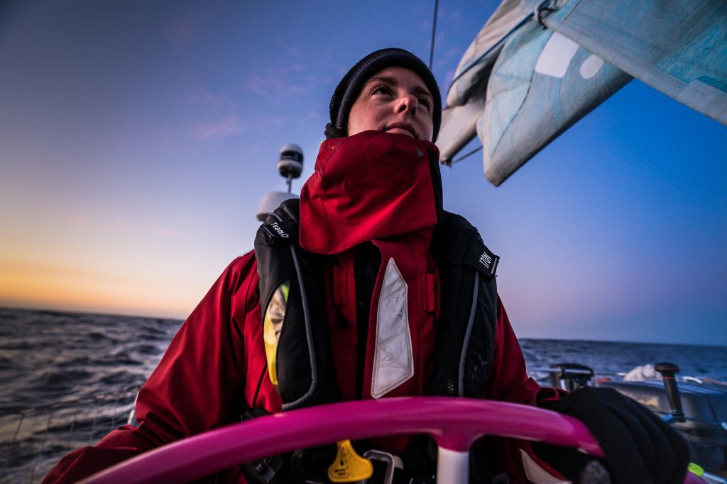 Erica stands at the helm in full foul weather gear with the sunset behind