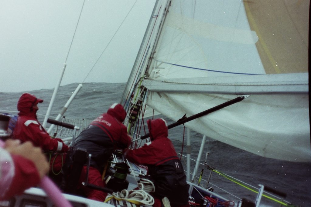 Two sailors on the grinder on Maiden. The boat is at an angle. Someone grips the helm. The waves are huge.